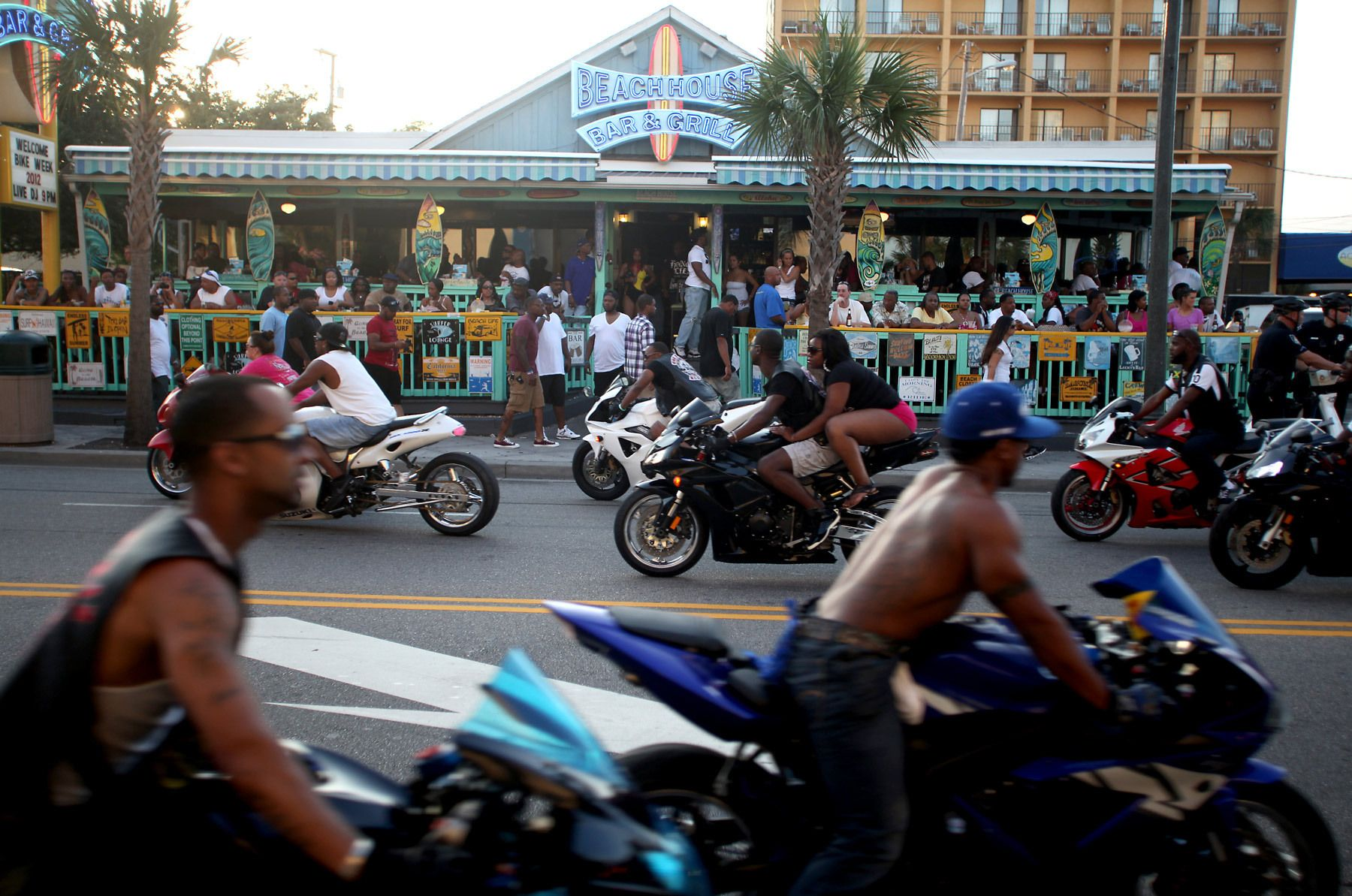 Bikers cruise down North Ocean Boulevard in front of the Beach House Bar and Grill Thursday evening in Myrtle Beach during the Atlantic Beach Memorial Day Bikefest. The bar is popular with onlookers and bikers because of the front patio overlooking the boulevard. Although centered in nearby Atlantic Beach, the Bikefest has spread to neighboring beaches in the Grand Strand region of the coast. (Photo By Randall Hill, For The Washington Post)