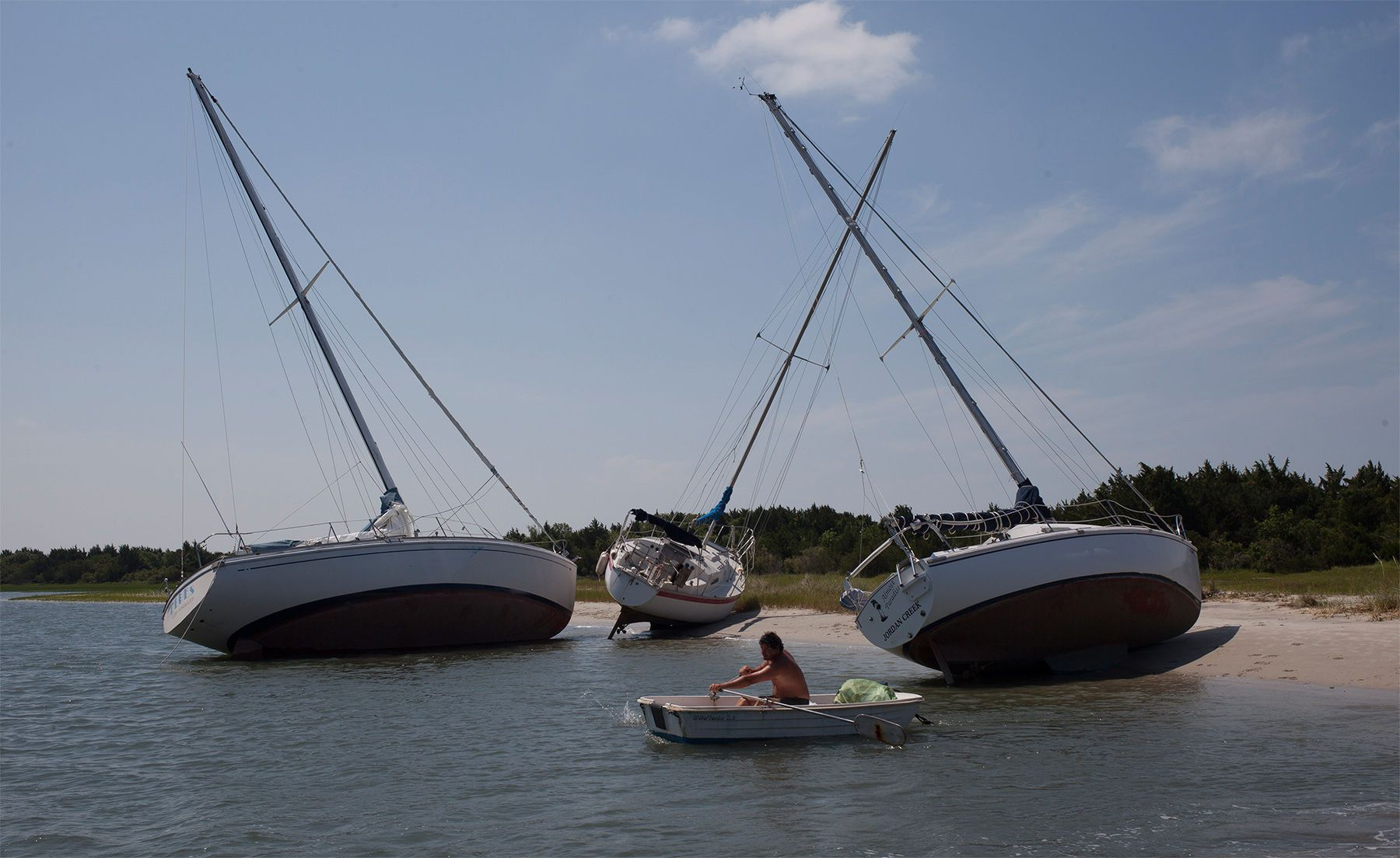 Jim Bonavito of Beaufort, North Carolina, rows his dingy past sailboats that broke free of their moorings during the winds and waves from Hurricane Arthur in Beaufort, North Carolina, Friday, July 04, 2014. Damage was scattered and light along the North Carolina coast near where the eye of Hurricane Arthur came ashore on Thursday evening.   (AP Photo/Randall Hill)