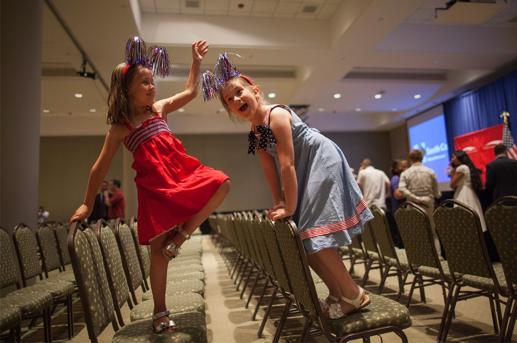 Sisters Sophia (L) and Norah Boice of North Charleston play on the seats after U.S. Democratic presidential candidate and former Secretary of State Hillary Clinton spoke at a rally at Trident Technical College Conference Center in North Charleston, South Carolina June 17, 2015.   REUTERS/Randall Hill