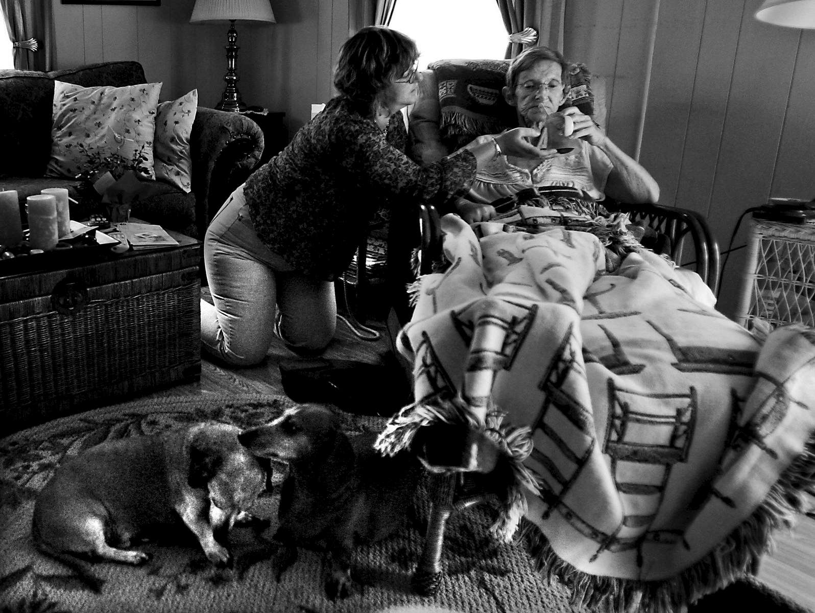 Cassie helps Pat with a drink of coke as Pat's 4-year-old dachshund Gretel grooms the 14-year-old Wrinkles at Pat's home in Conway.