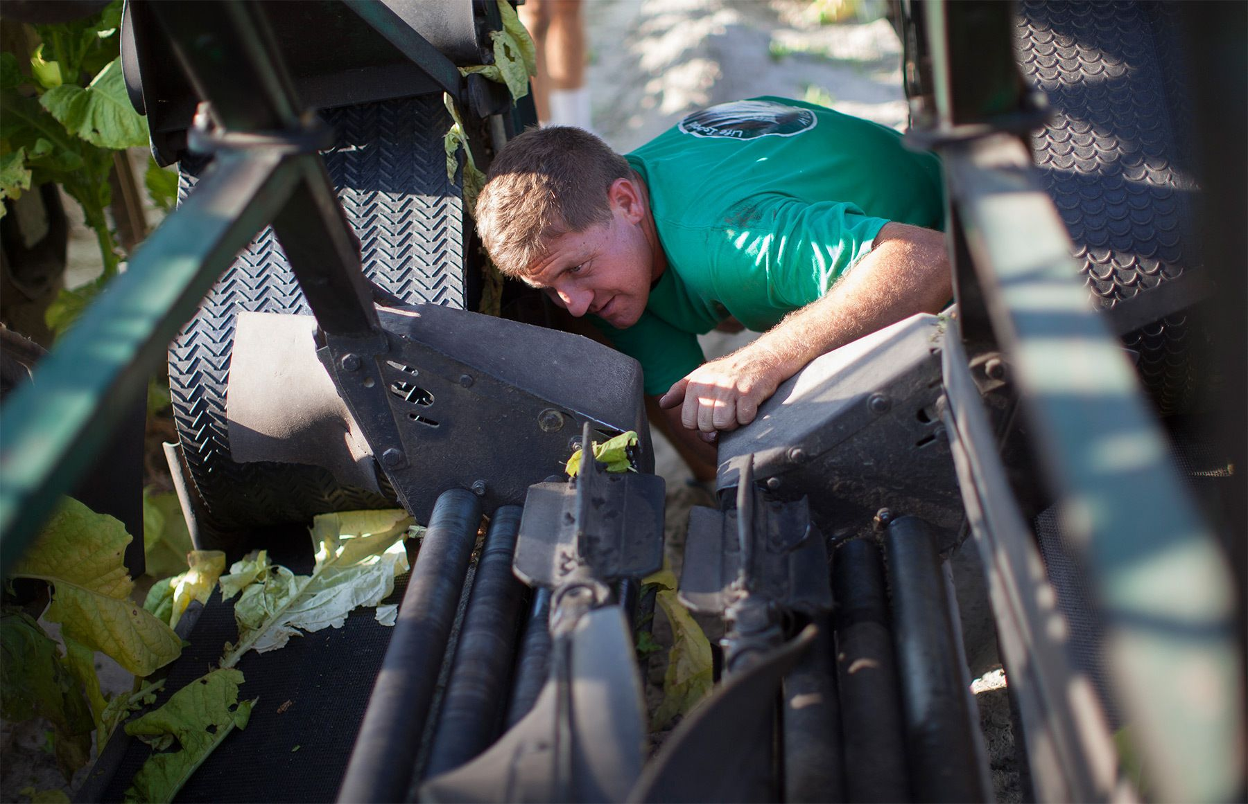 Fourth generation farmer Cam Shelly works to repair a tobacco harvester at Shelly Farms in the Pleasant View community of Horry County, South Carolina July 26, 2013. The traditional tobacco harvest requires many labor intensive hours to bring the crop to market, especially with the flue-cured variety prominent in the southern United States. With the growing health concerns with smoking in the US, most farmers use market cooperatives to sell their crop to the growing markets in China.     Picture taken on July 26, 2013.   REUTERS/Randall Hill (UNITED STATES)