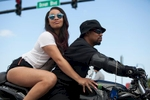 A biker and his rider check out the sights on Ocean Boulevard during the 2015 Atlantic Beach Memorial Day BikeFest in Myrtle Beach, South Carolina May 22, 2015. After three people were killed and seven wounded in shootings during 2014 Bikefest, State officials called for an end to the event that draws thousands to the family-friendly beach town.Their efforts were unsuccessful. Bikers returned to Myrtle Beach - just a week after a bloody motorcycle gang shootout in Waco, Texas. But this time authorities are more prepared, with dozens of new surveillance cameras and a police force three times the size of last year's.    REUTERS/Randall Hill