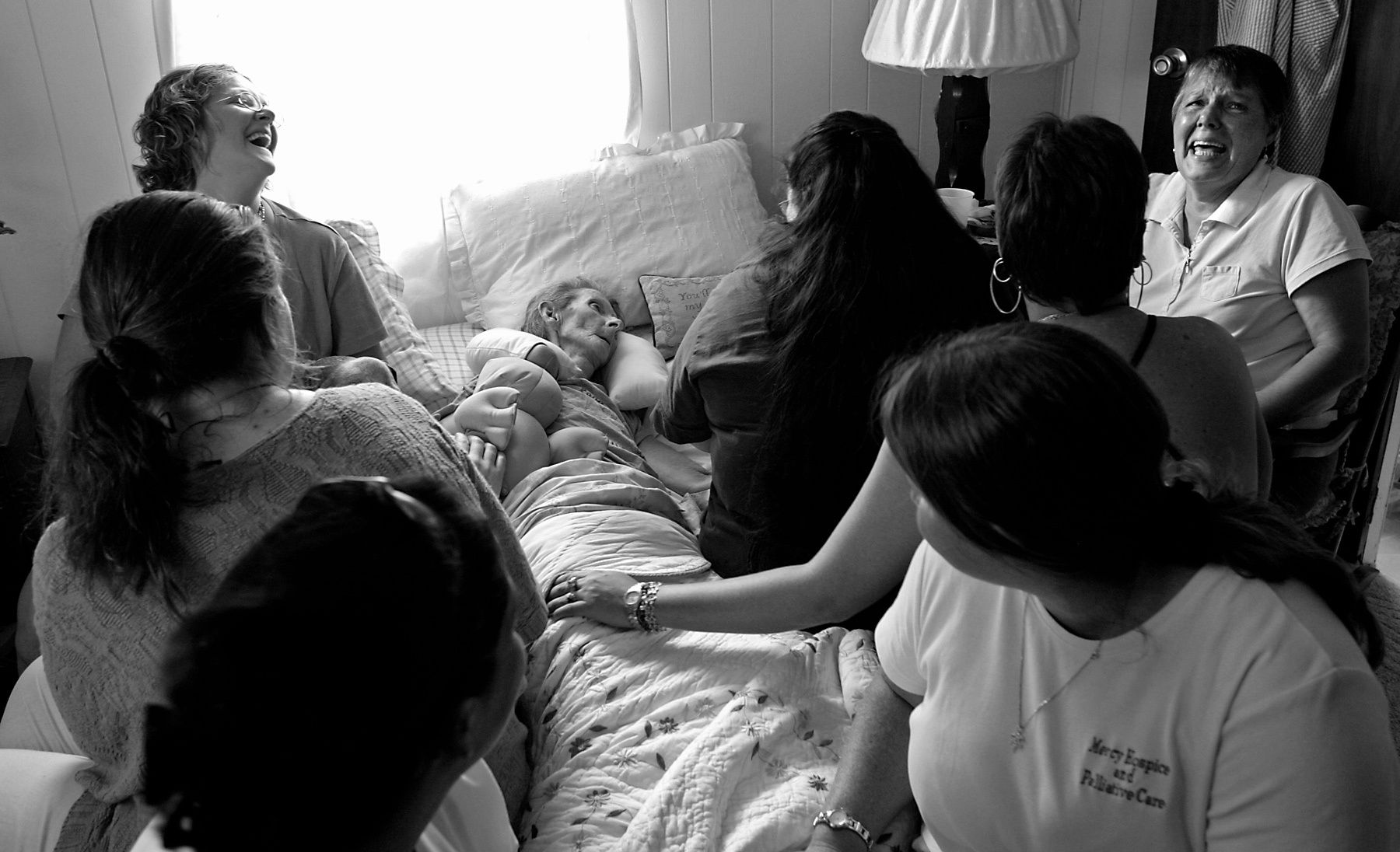 Family, friends and co-workers of Mercy Hospice, share humorous stories about Pat in a crowded bedroom on the afternoon before she died of Colon Cancer.{quote}She would of told us as we sit here,{quote} said friend J.J. Daniel. (far right) {quote}Grow-up and handle this with your big girl panties on.{quote}