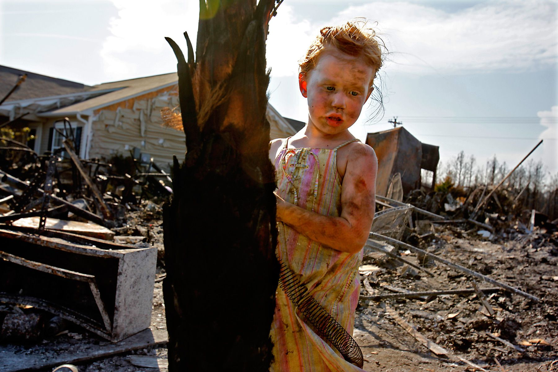 Covered in soot from helping with the search for keepsakes at her grandparent's burnt out house on Swift Street in Barefoot Resort, Elli Boos, 4, plays with a bedspring on Friday used as a toy. With her parents Derek and Penny Boos and other siblings, the grandchildren of Bob and Jo Ann Portteus played an important role in helping with the search for usable personal items. Residents living in the fire affected areas were allowed back to their homes today to check on the status of their homes. The Portteus home was one of several  completely damaged on Swift Street in the development. {quote}It's just good having a loving family,{quote} said Bob Portteus when asked how he felt about the damage to his home and watching his family helping with the search. {quote}Everything else can be replaced.{quote}