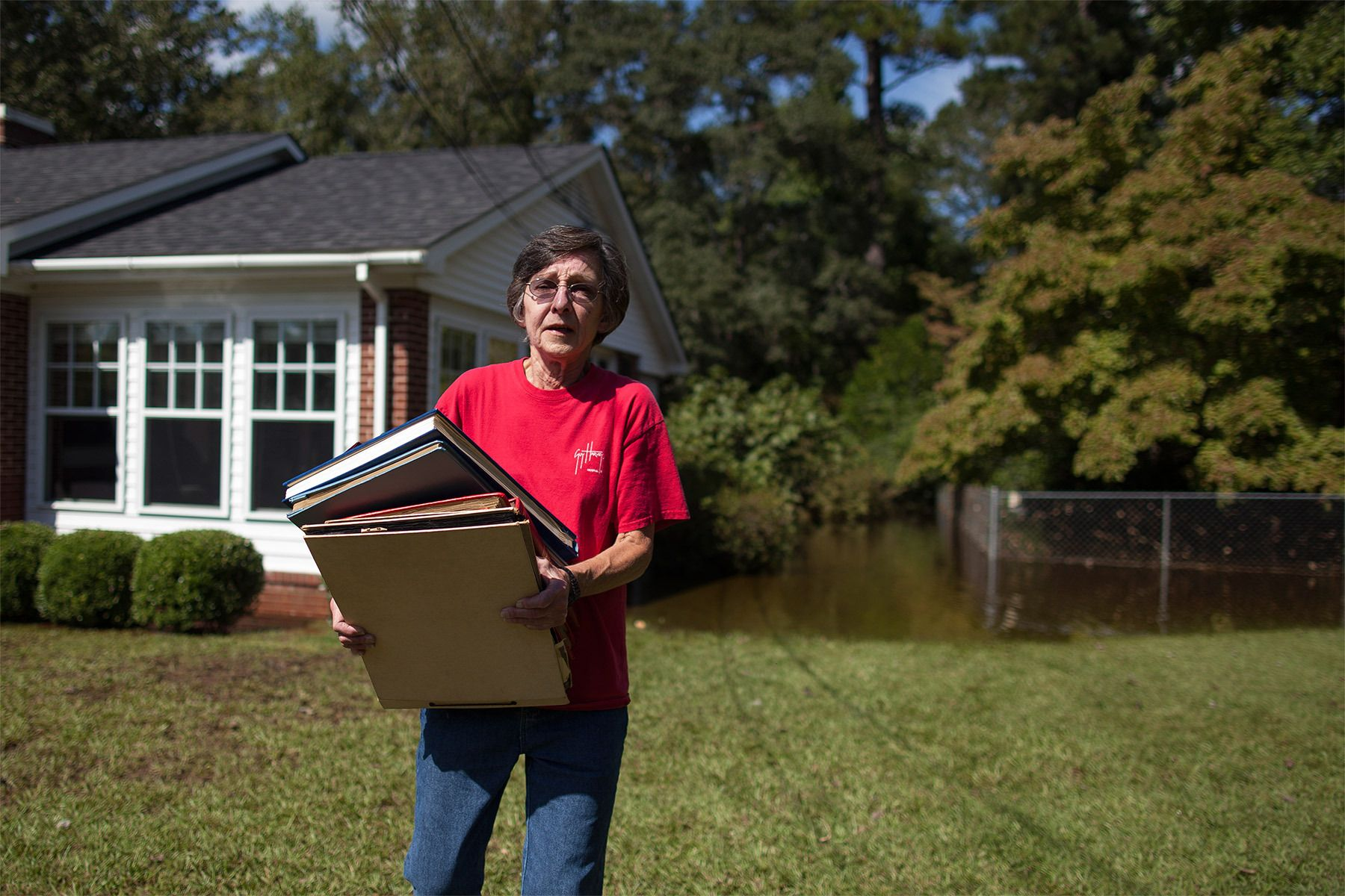 Deborah Hanna of Kingstree rescues old photographs from her mother's flooded home on Singleton Avenue in Kingstree, South Carolina October 8, 2015. The family was able to return to the home after evacuating on Sunday. Flooding from historic rainfall in South Carolina claimed two more lives on Wednesday, and the threat of further inundation from swollen rivers and vulnerable dams put already ravaged communities on edge.  REUTERS/Randall Hill