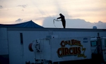 With heavy winds throughout the area, a worker secures a trailer during the Cole Brothers Circus of the Stars stop in Myrtle Beach, South Carolina March 31, 2013. Traveling circuses such as the Cole Brothers Circus of the Stars, complete with it's traveling big top tent, set up their tent city in smaller markets all along the East Coast of the United States as they aim to bring the circus to rural areas. The Cole Brothers Circus, now in its 129th edition, travels to 100 cities in 20-25 states and stages 250 shows a year.   REUTERS/Randall Hill   (UNITED STATES)