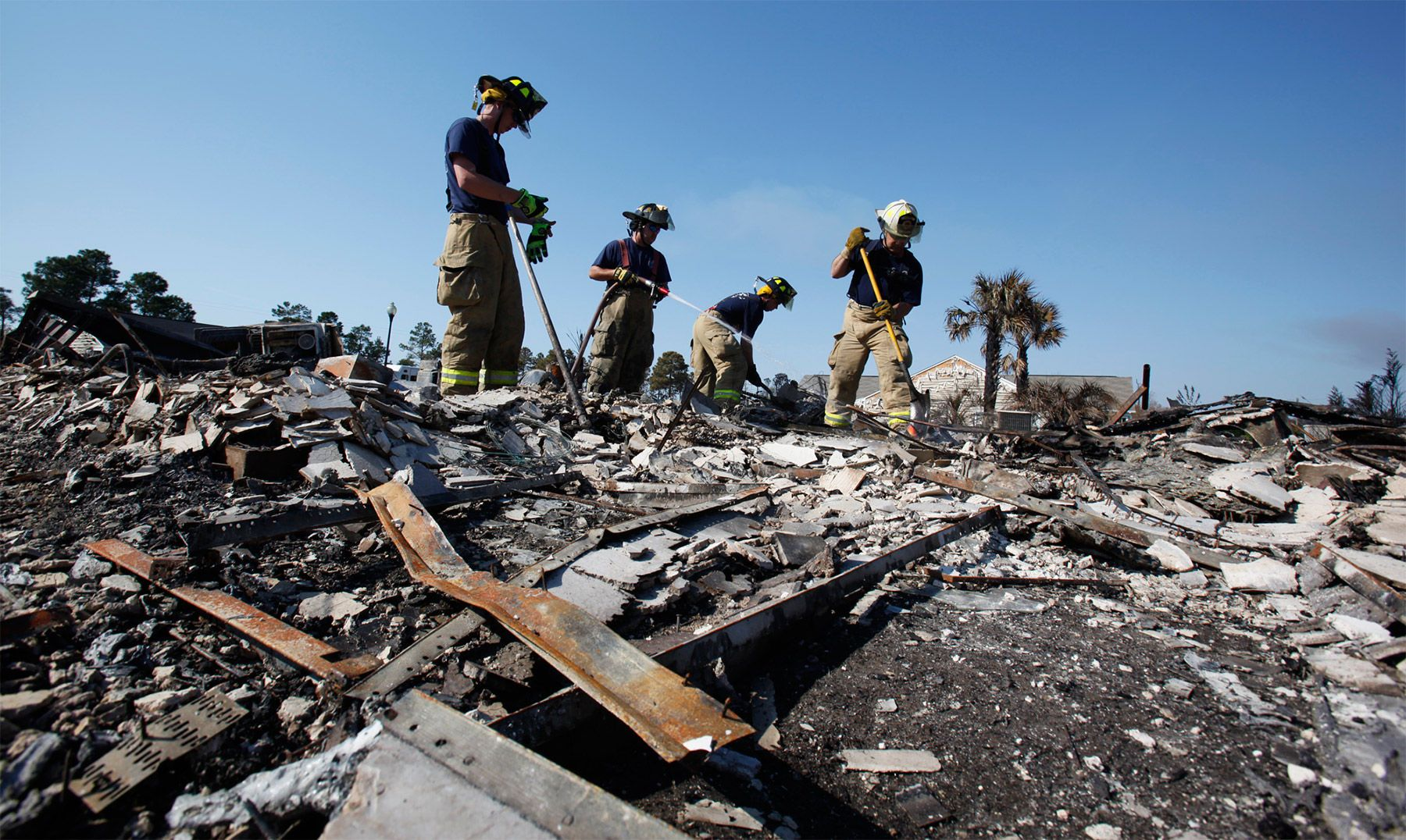 Firefighters with the Sumter Fire Department work to put out hot spots on Swift Street in Barefoot Resort Friday afternoon in North Myrtle Beach.