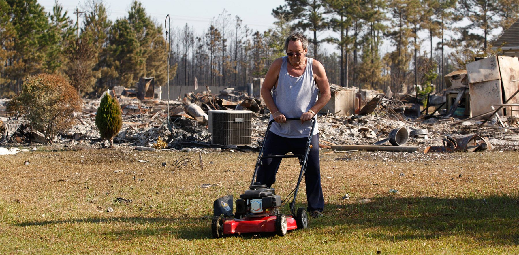 With his neighbor's house in the background in ruin, Robert Whitlock of Marsh Glen drive in Barefoot Resort, mows his yard Friday afternoon in North Myrtle Beach. {quote}The waterway probably went down three foot I used so much water to save it,{quote} said Whitlock about the five hours he watered his house Thursday morning to keep it from the firestorm.