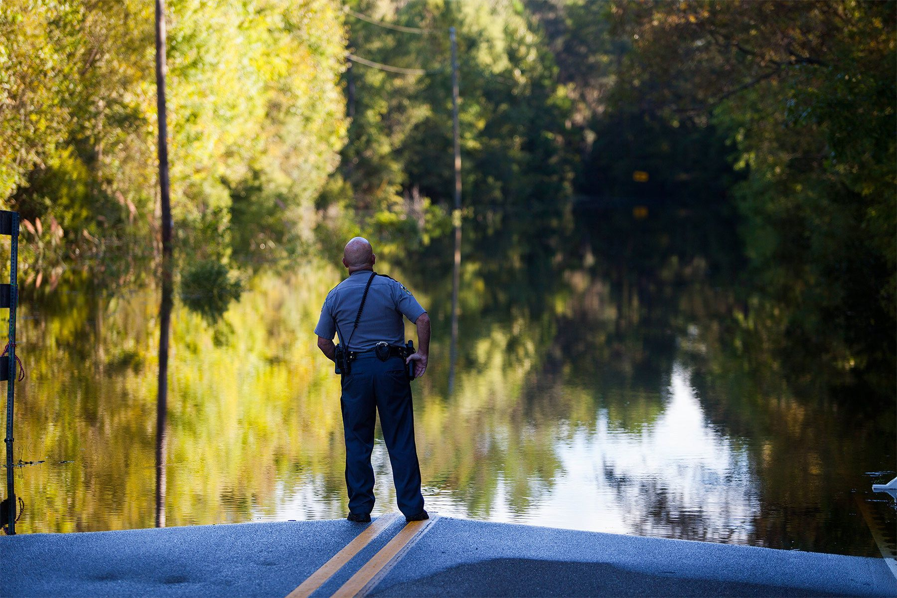 Horry County police officer Jeff Helfinstine patrols the edge of flood waters along Lee's Landing Circle in Conway, South Carolina October 7, 2015. Rescuers searched early Wednesday for two people missing in floodwaters in South Carolina, while authorities urged residents in hundreds of homes to seek higher ground. REUTERS/Randall Hill