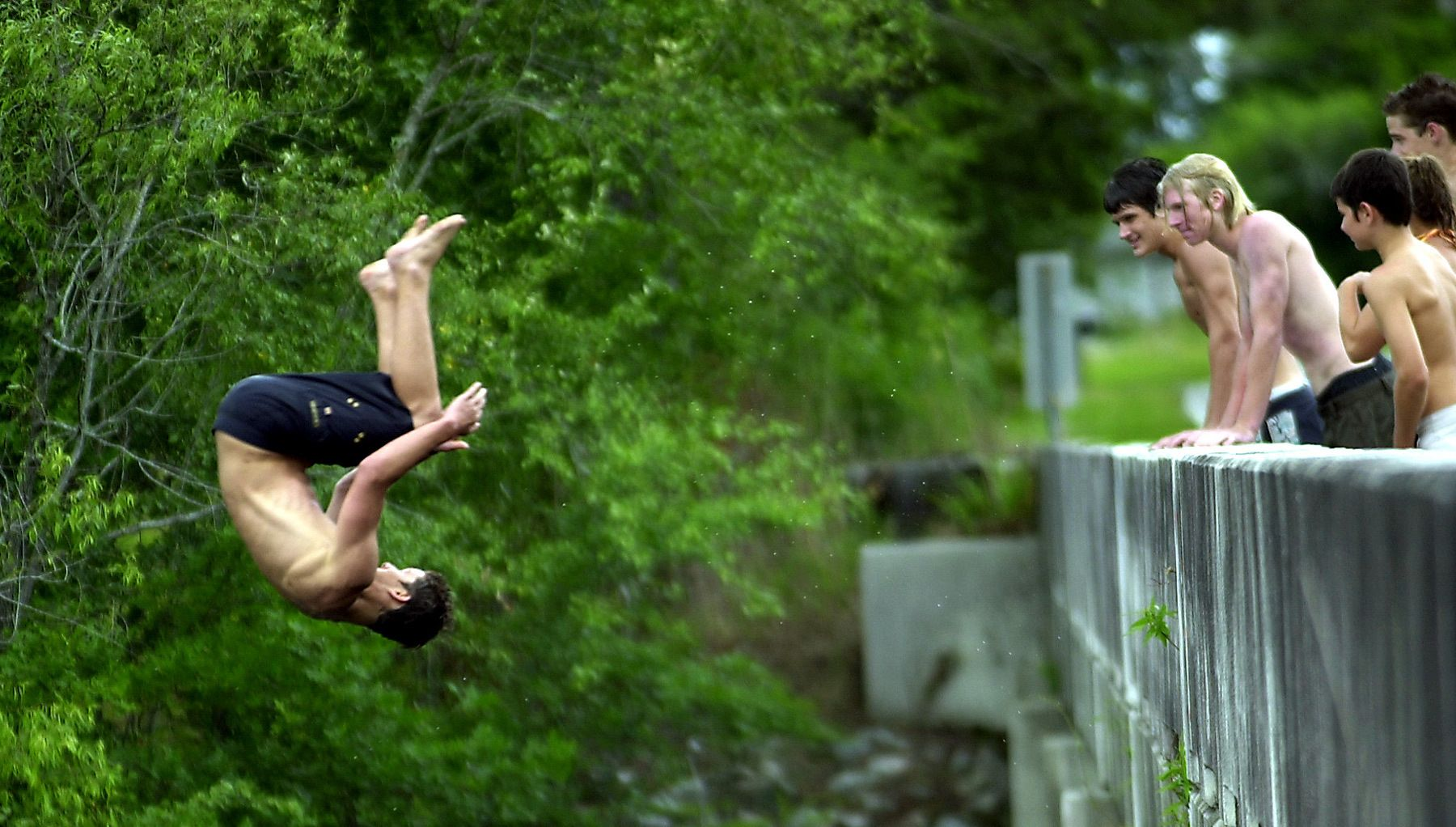 Friends watch as Josh Walker,17, of Myrtle Beach does a somersault off the Red Bluff Landing bridge and into the cool waters of the Waccamaw River in rural Horry County. The top of the bridge is about 25 feet above the river.
