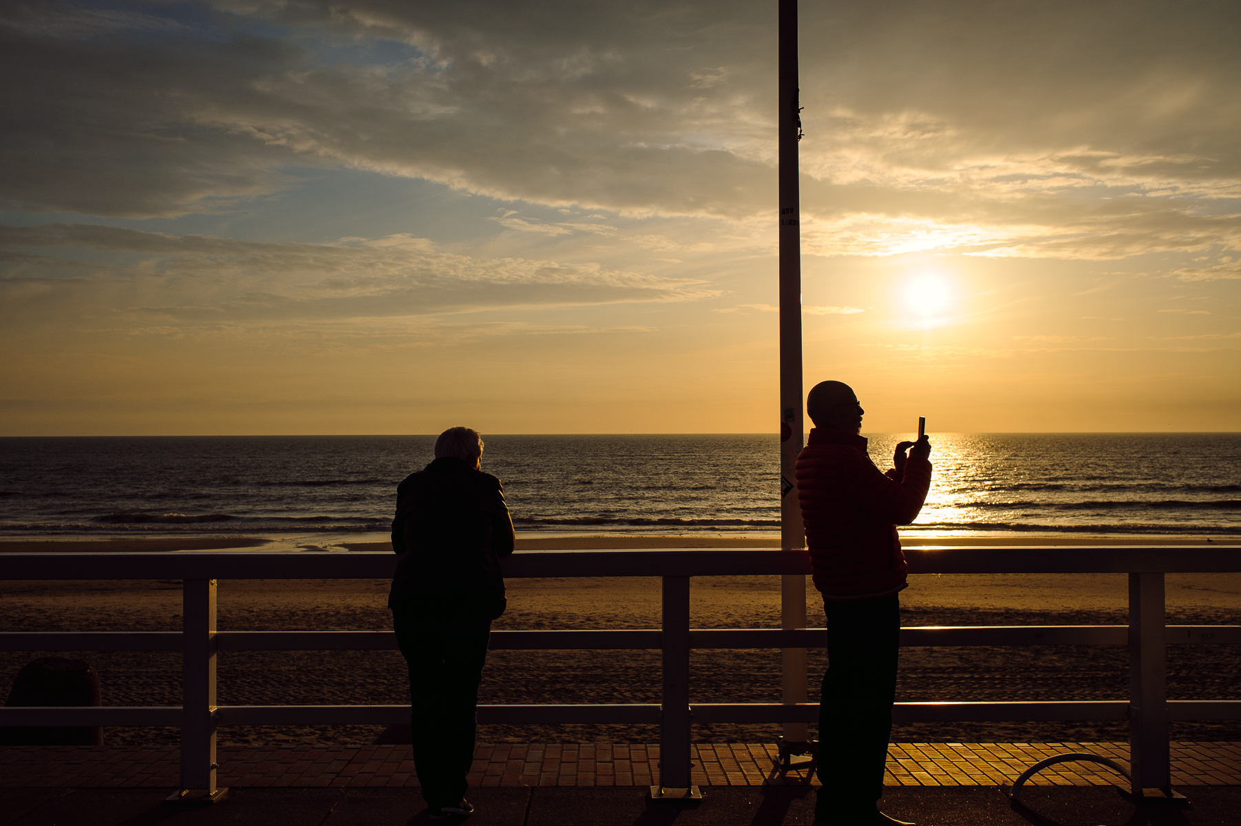 While mom watches the sunset, dad takes a picture of the beach panorama on the promenade in Westerland. Sylt, Germany, June 16, 2018.