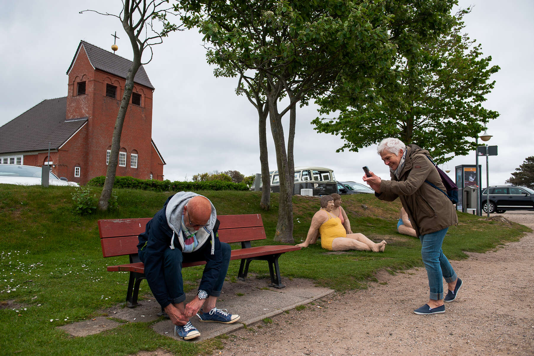 Having reached the pond in Wenningstedt on their way home from the Braderuper Heide, mom photographs dad fastening his shoelaces. Sylt, Germany, May 25, 2019.