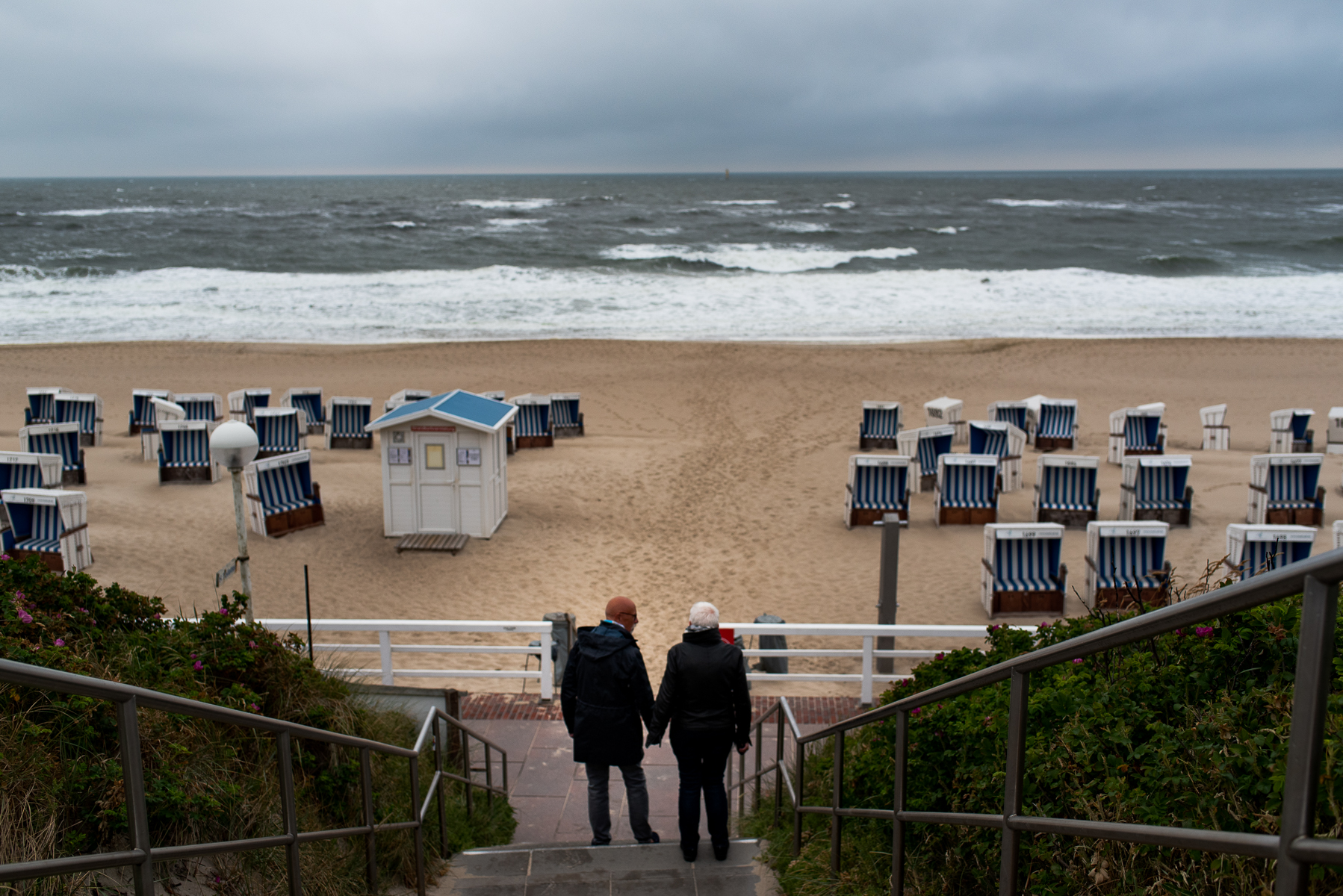 Mom and dad look over the ocean before starting an evening walk along the promenade in Westerland. Sylt, Germany, June 20, 2018.