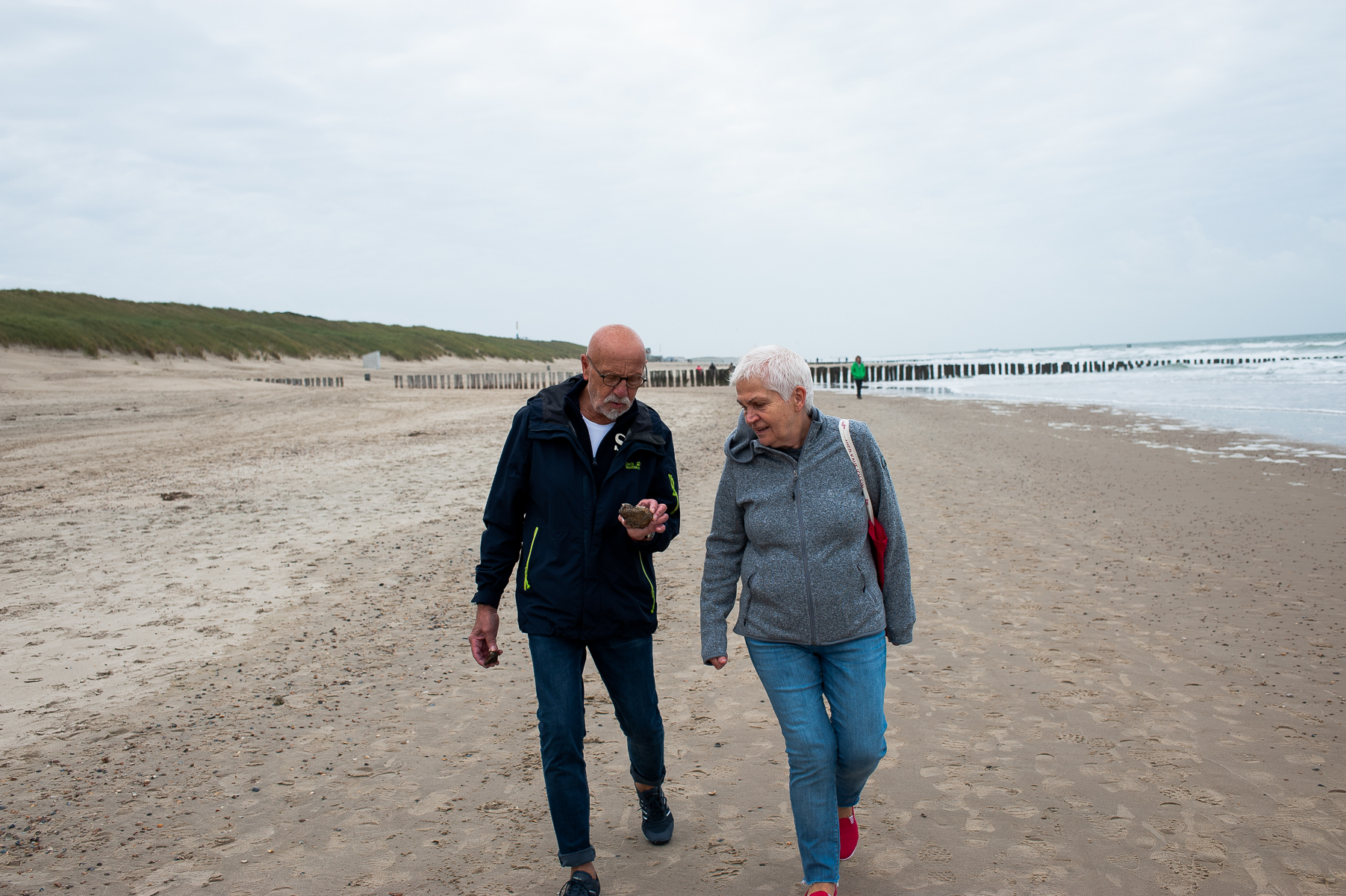 Dad shows mom a pebble he's found on the beach. Domburg, Netherlands, October 8, 2019.