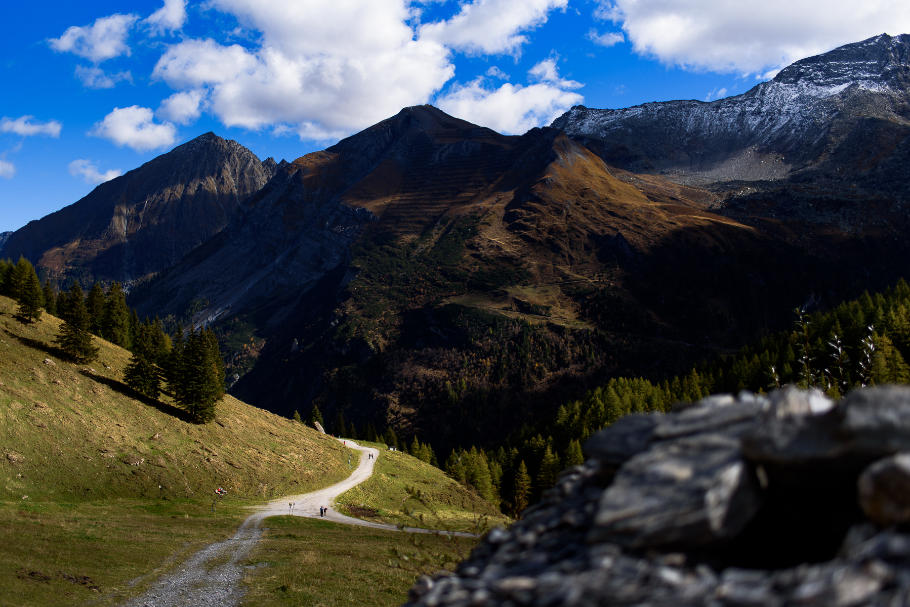 Mom and dad walk in the distance with the mountains of the Hintertux area in the background. Starting their walk at the Hintertux summit station, the destination is the rest station Bichl Alm, before the walk continues back down to the Hintertux valley station. Austria, October 8, 2018.