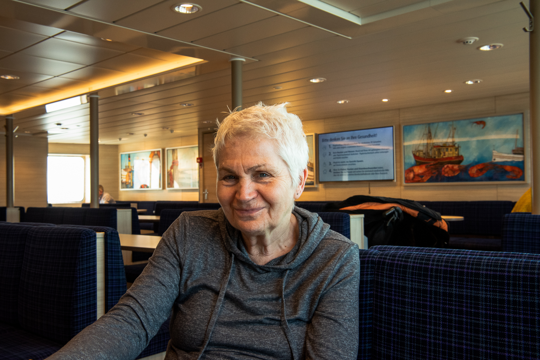 Mom onboard the ferry from Norddeich to Norderney. Another sign of the developing pandemic are the hygiene guidelines posted on the ferry's screen in the background. Norderney, Germany, March 5, 2020.