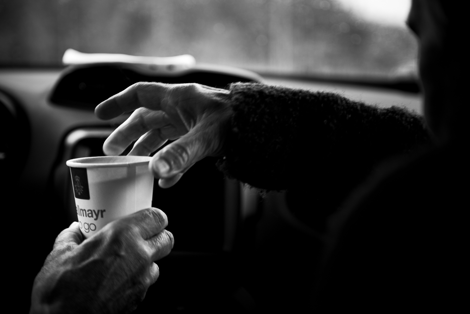After a quick breakfast snack at an autobahn rest stop, mom hands dad a cup of coffee. Germany, May 21, 2019.