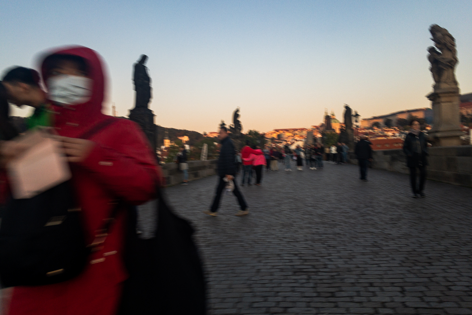 Charles Bridge is the tourist attraction in the heart of the city. Sometimes you have to squeeze through the mass of people on the bridge. Here I pass a woman who's got her phone at the ready for a snapshot while a wall of people in the background tries to grab a shot of sunrise over the old town. Prague, Czechia, September 22, 2019.