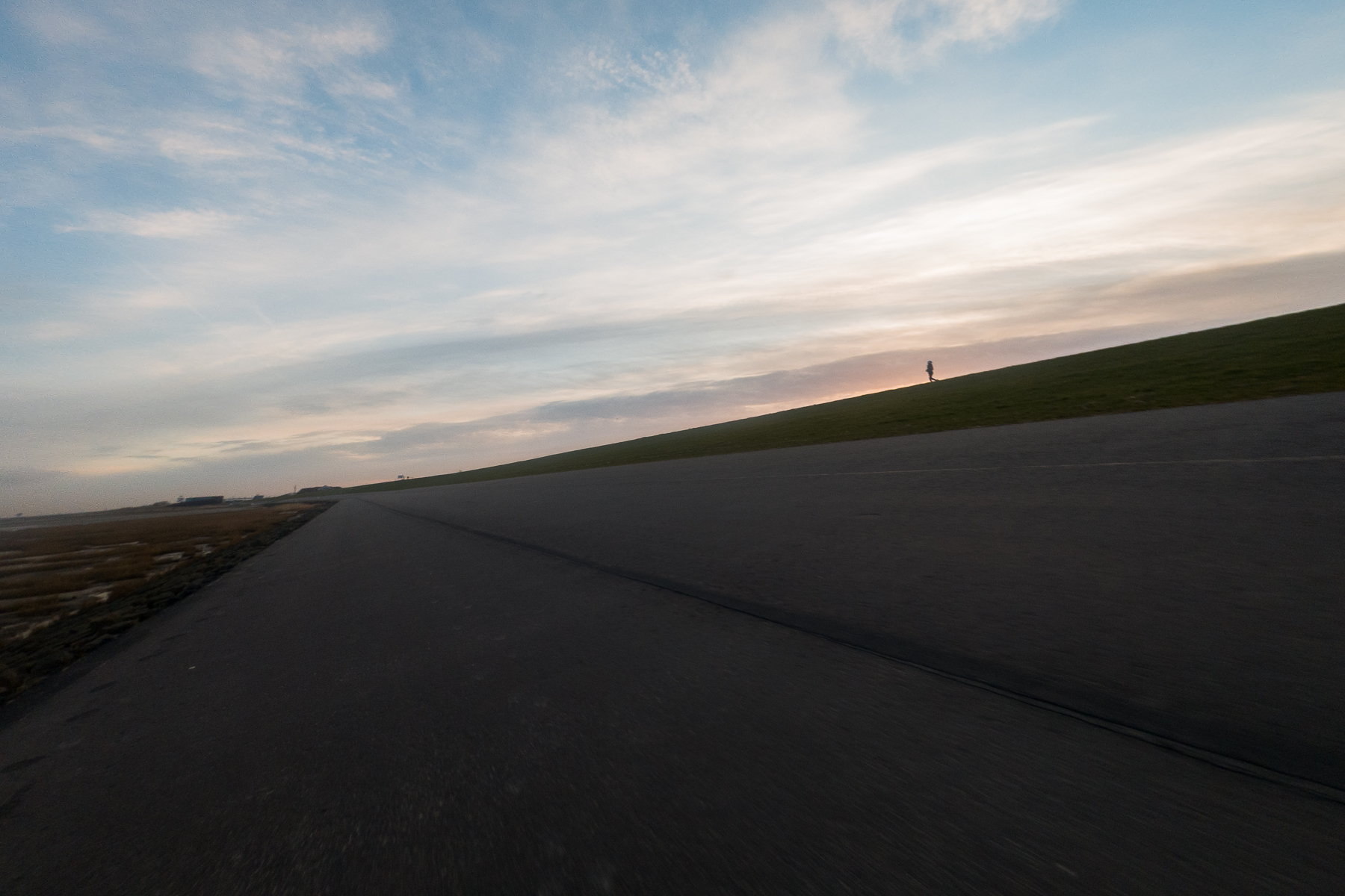 A calmer morning a few kilometers west, with the Wadden Sea to the left and a fellow runner on the levee to the right. Norddeich, Germany, March 8, 2020.