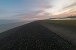 The fresh air and the serenity of ocean views make up for uneven surfaces and heavy winds. Pictured here the view from the stretch of a levee that eventually allows for access to the harbor (to the right). Norddeich, Germany, March 5, 2020.